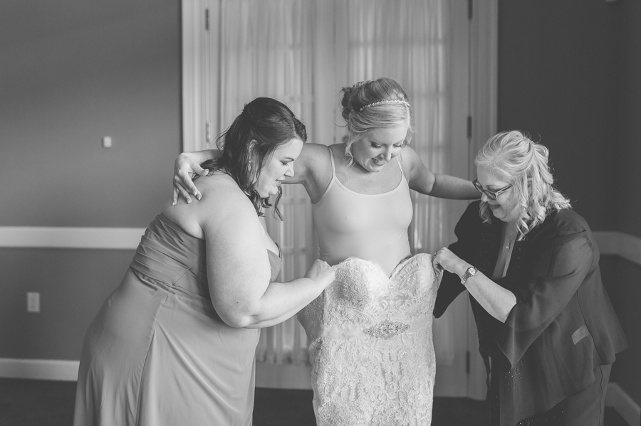 black and white photos of bride getting into wedding dress