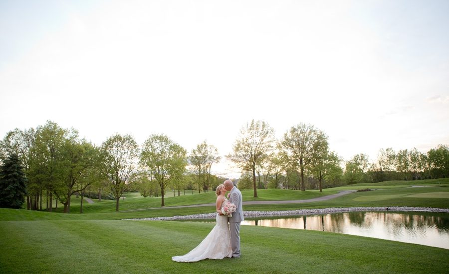 couple kissing by water at wedgewood country club
