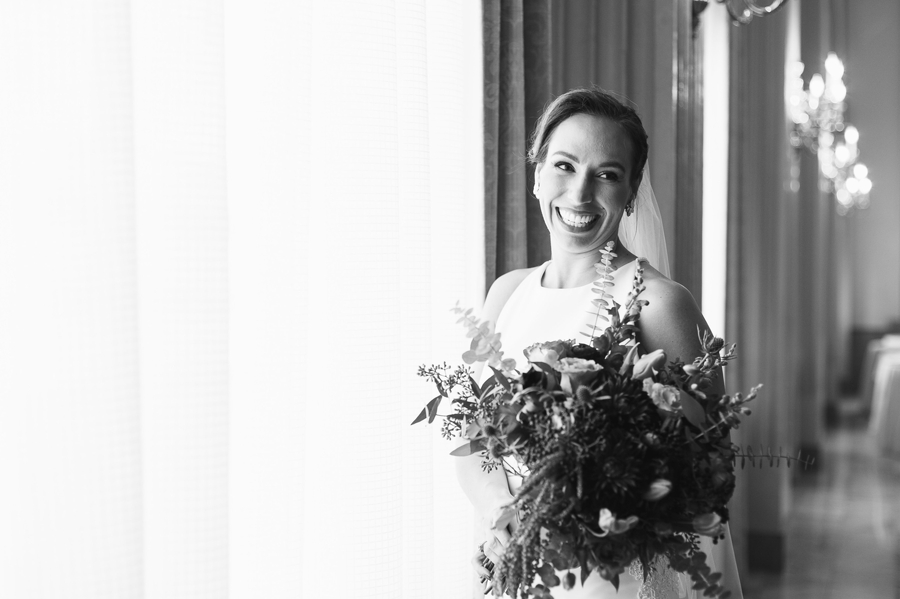 black and white photo of the bride by window