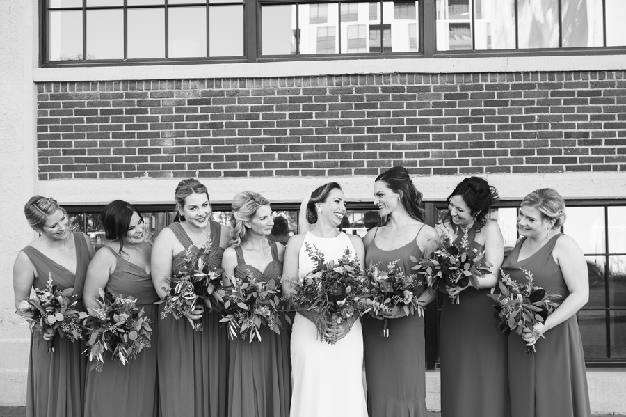 black and white photo of bride smiling at bridemaids