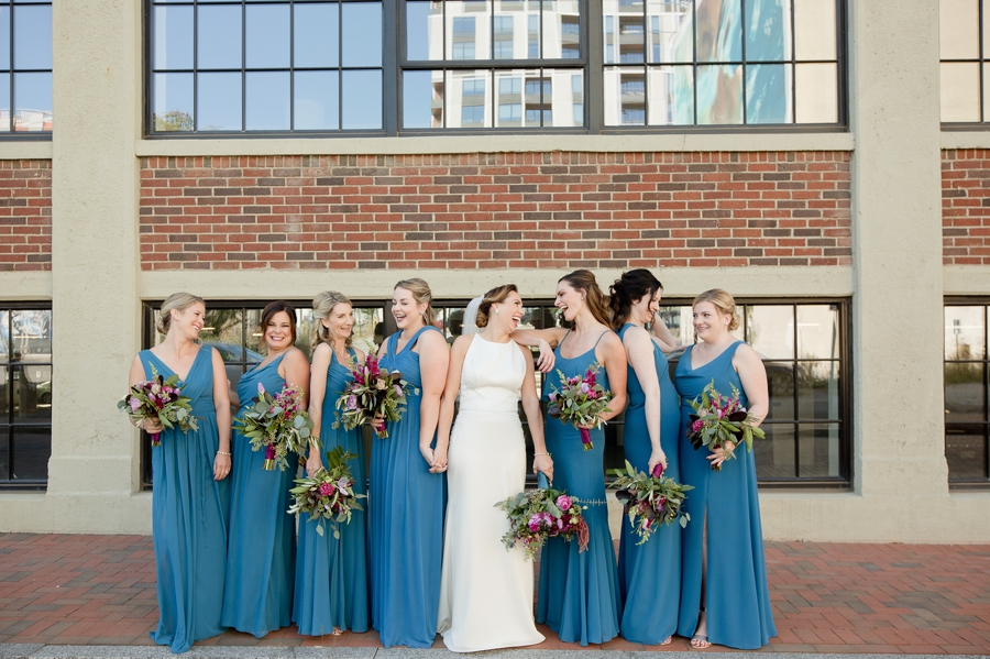 bride holding hands with bridesmaid laughing