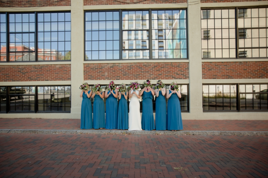 bride and bridesmaids covering faces with bouquets