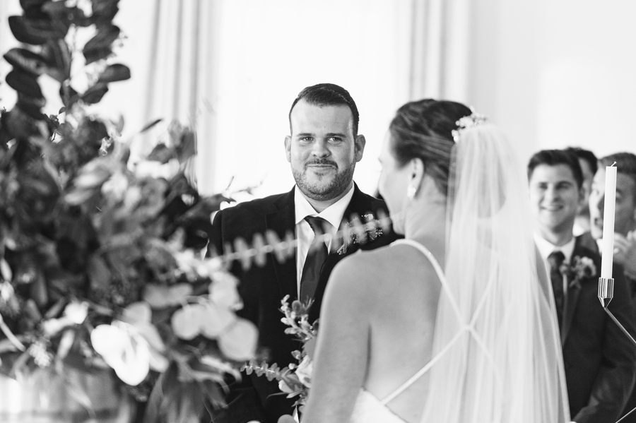 groom looking at bride smiling during ceremony
