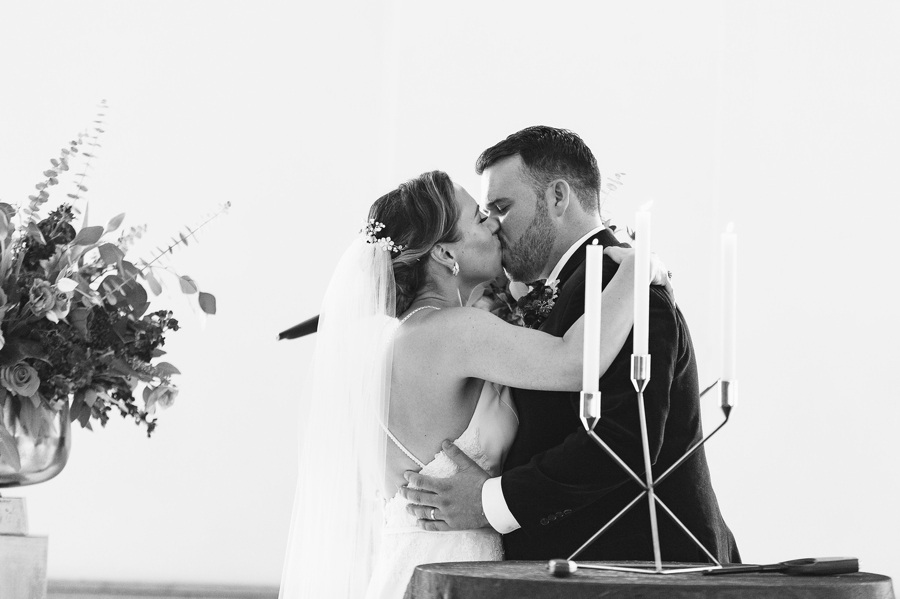 black and white photo of bride and groom first kiss