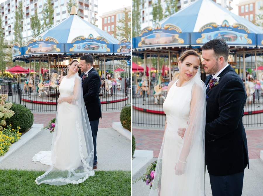 groom looking down at bride in front of carousel
