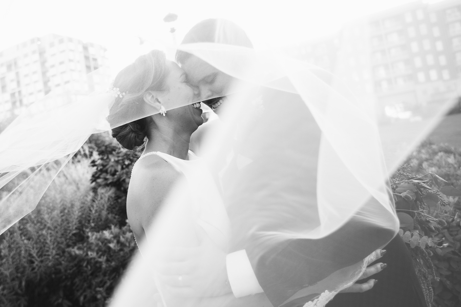 black and white photo of bride and groom under veil