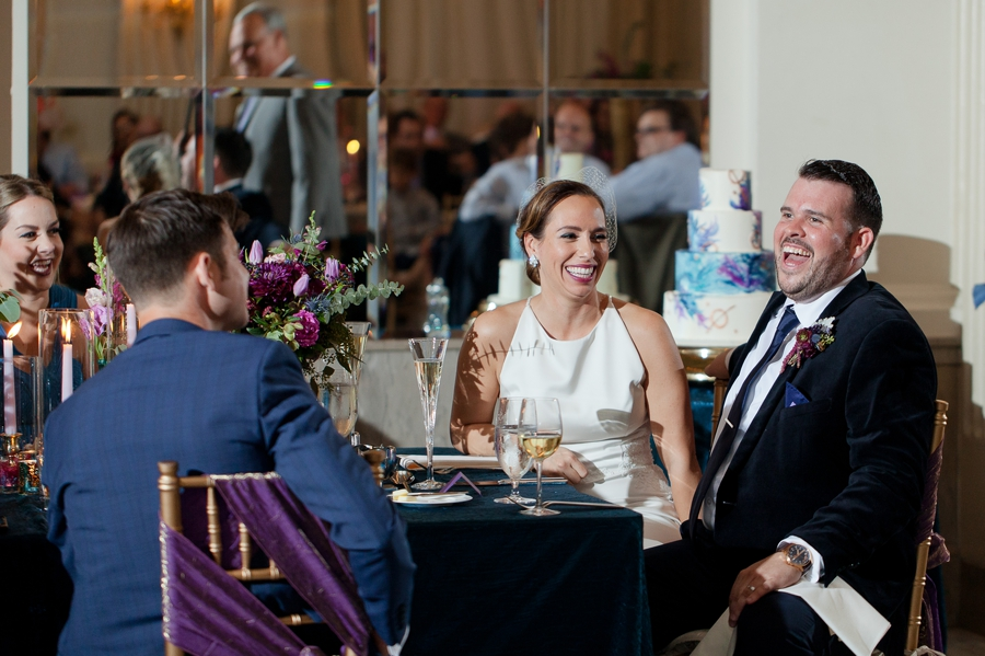 bride and groom laughing during father of groom speech