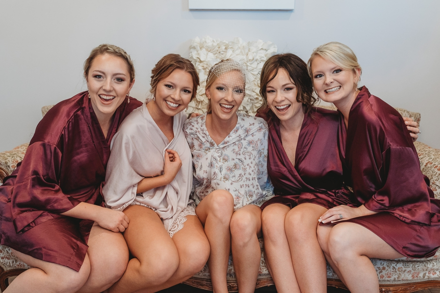 bride with bridesmaids on antique couch