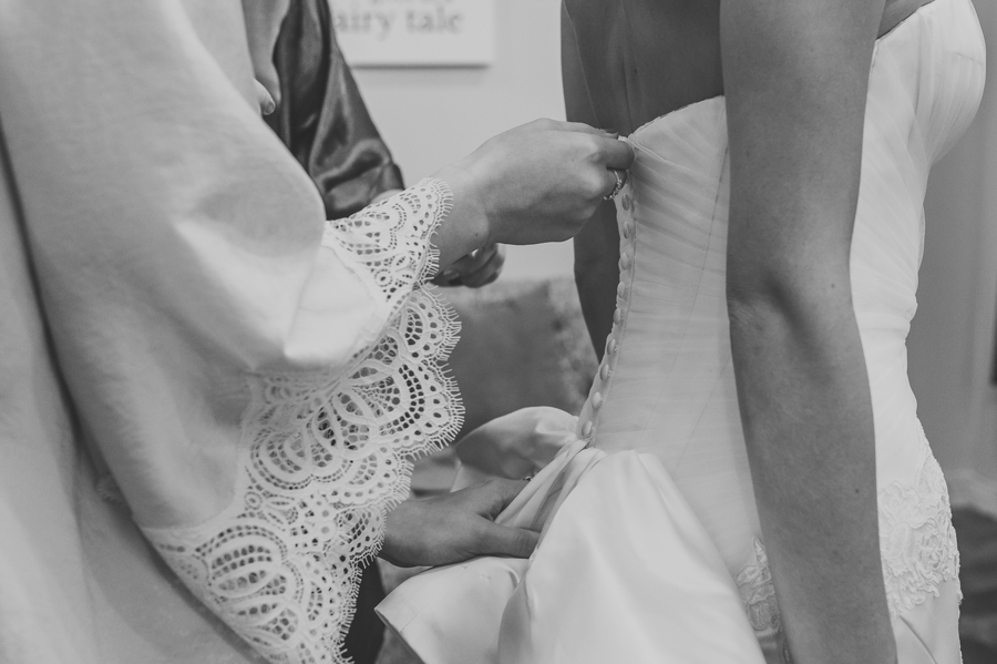 close up of brides dress getting zipped up