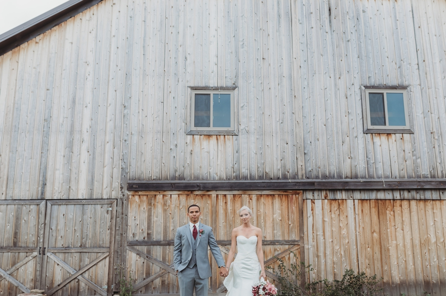 wide photo of bride and groom in front of barn at a winery wedding