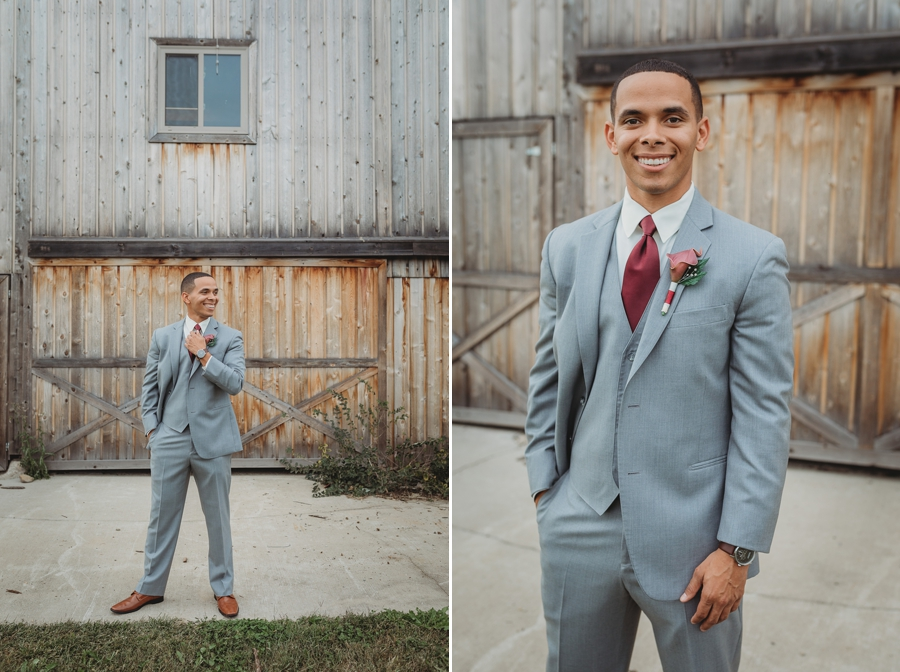 groom standing in front of barn adjusting tie at a winery wedding