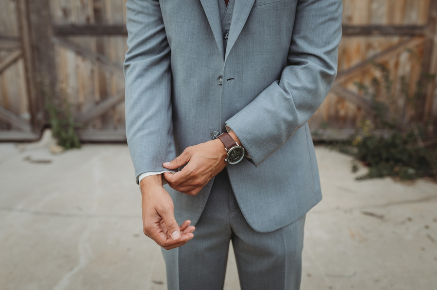 groom adjusting sleeves of suit