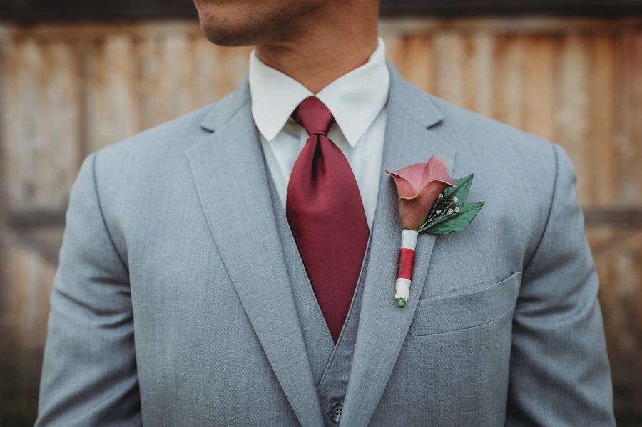 close up of grooms burgundy tie with gray suit