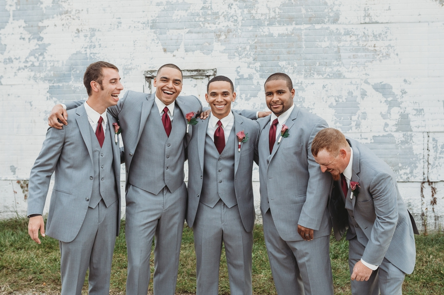 groomsmen cracking jokes at at a winery wedding
