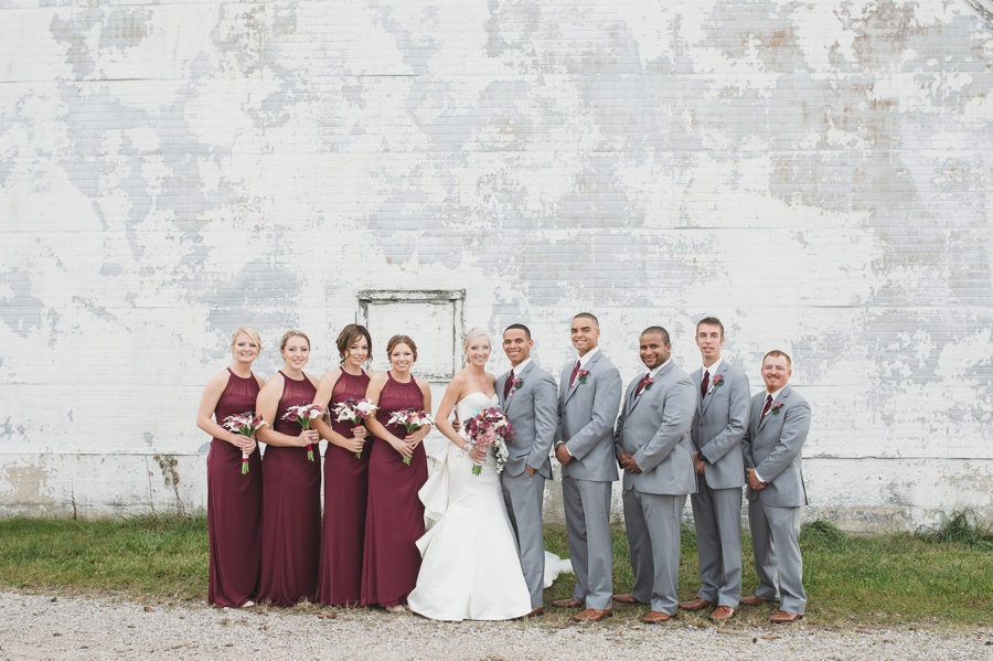 wide photo of wedding party in burgundy and gray