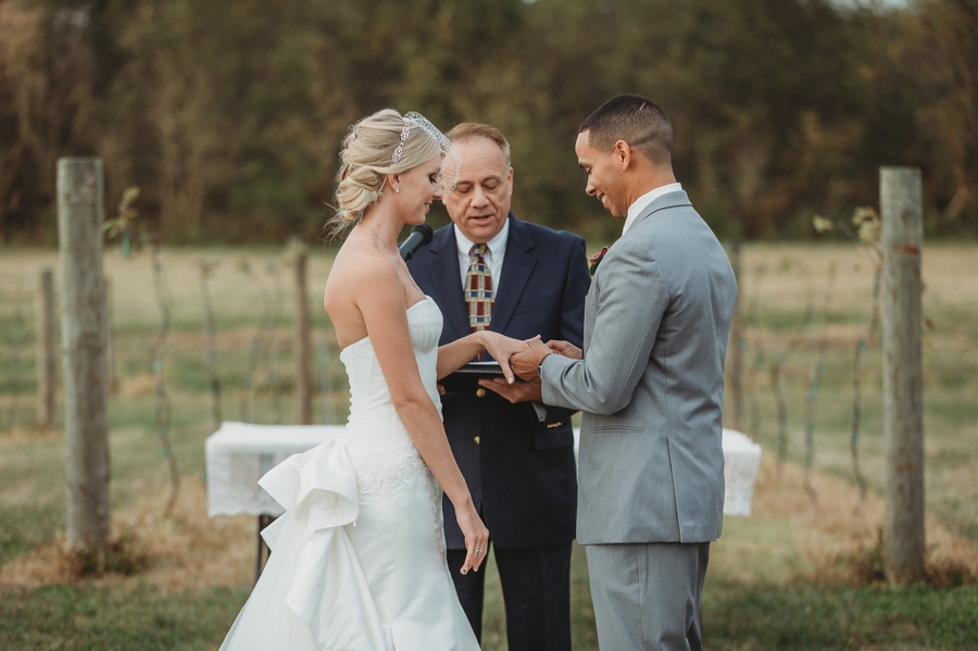 groom putting wedding ring on bride at at a winery wedding