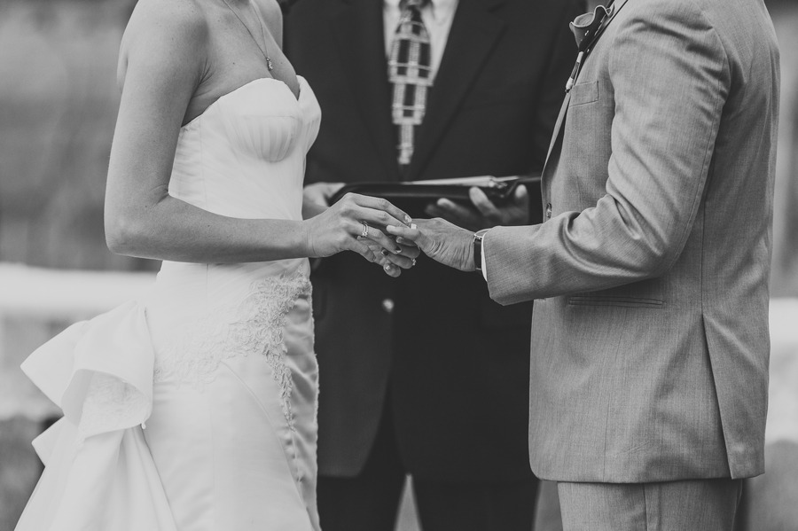 close up black and white photo of bride putting on grooms ring