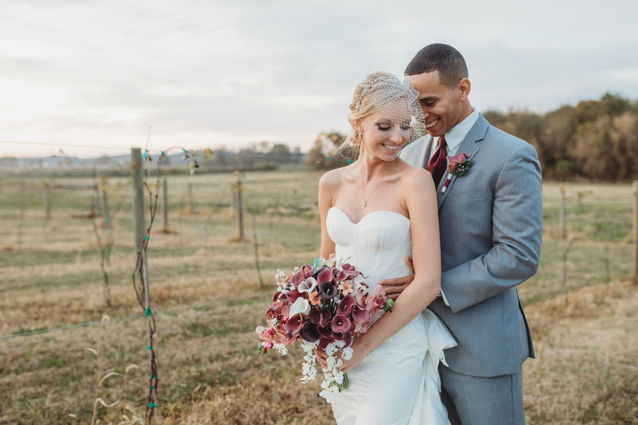 bride and groom snuggling in a vineyard at a winery wedding