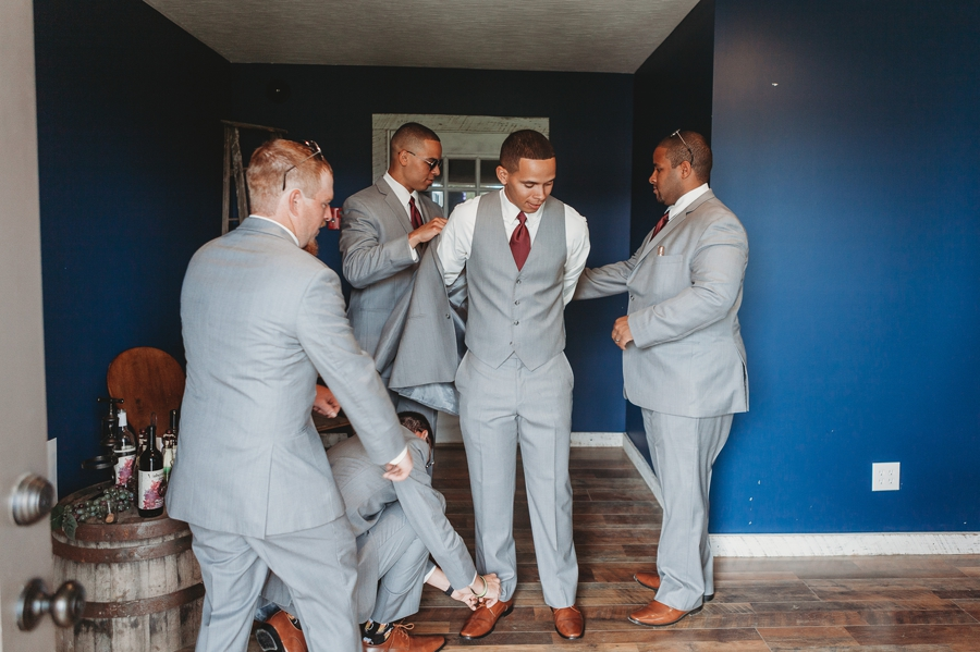 groomsmen helping groom get ready