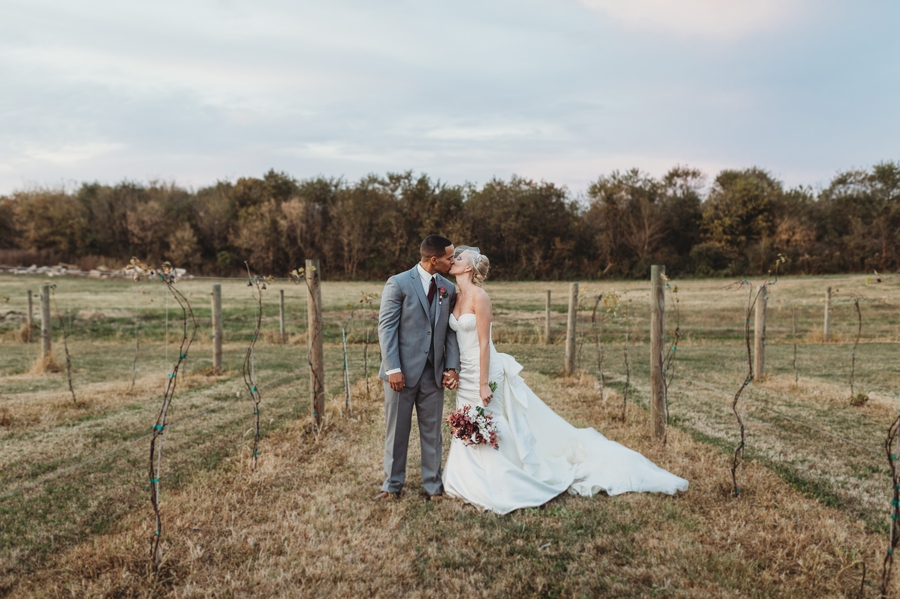 bride and groom kissing in a vineyard at vinberige vineyard winery wedding