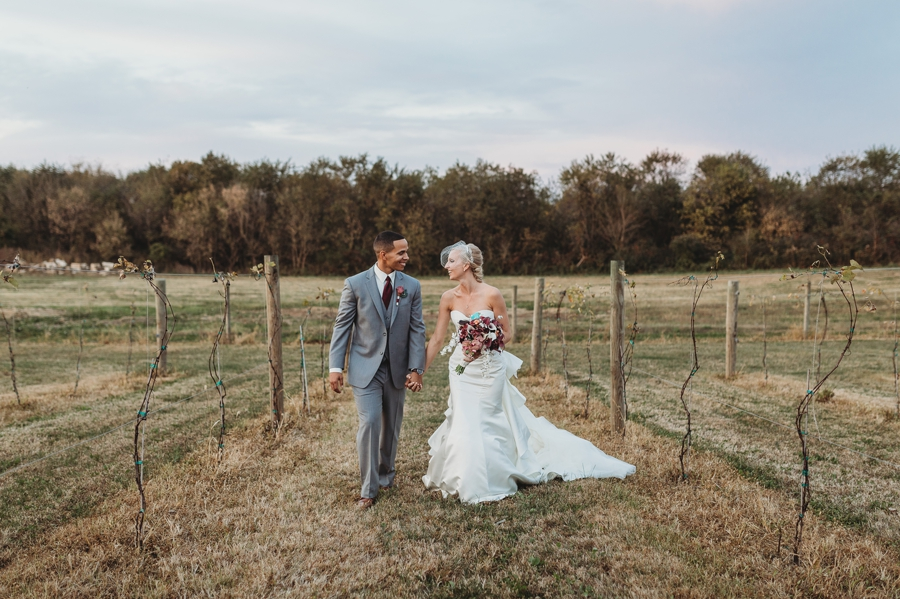 bride and groom walking in a vineyard at vinberige vineyard winery wedding
