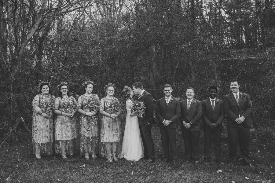 black and white photo of bride and groom with wedding party