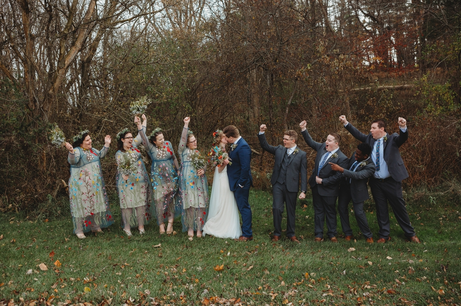 wedding party cheering on bride and groom during kiss