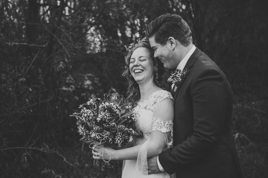 black and white photo of bride and groom laughing