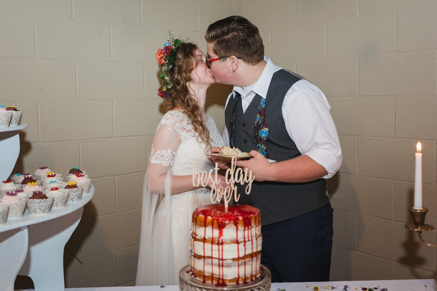 bride and groom kissing at cake cutting