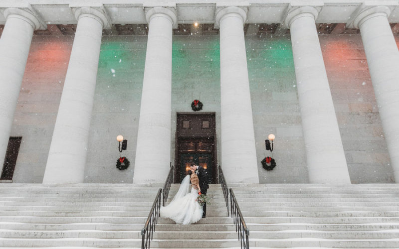 wide photo of couple kissing at The Ohio Statehouse in snow