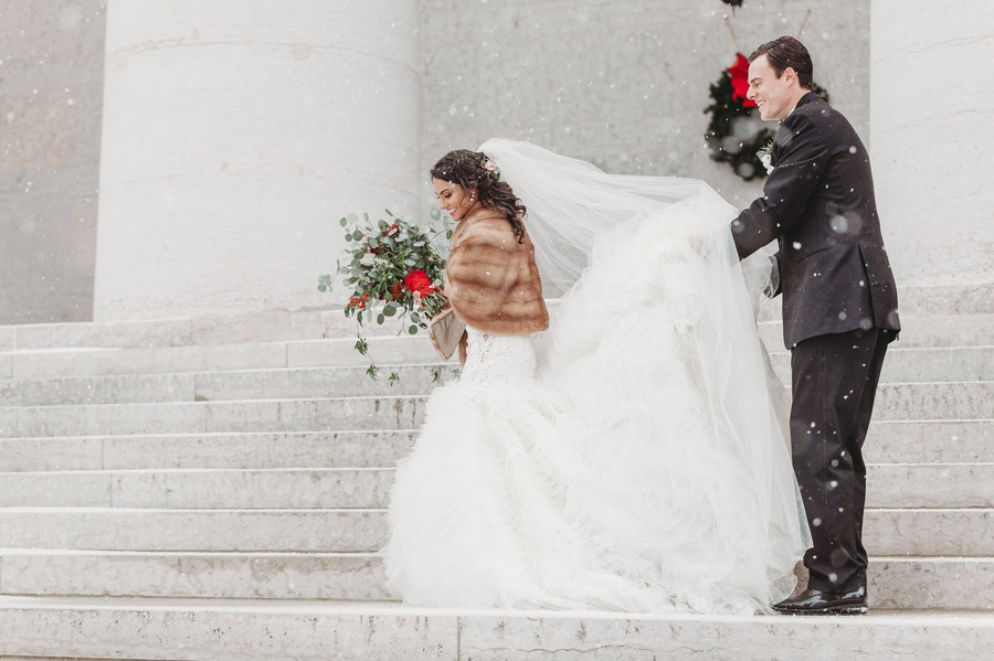 bride and groom walking in snow at Ohio Statehouse