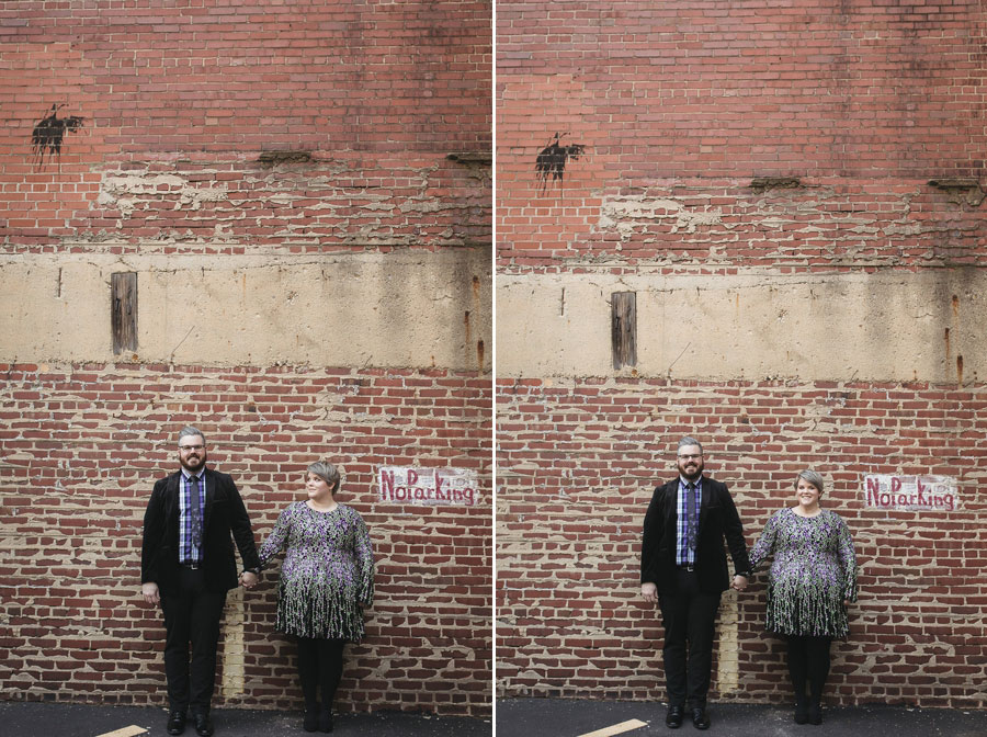 engaged couple holding hands on brick wall