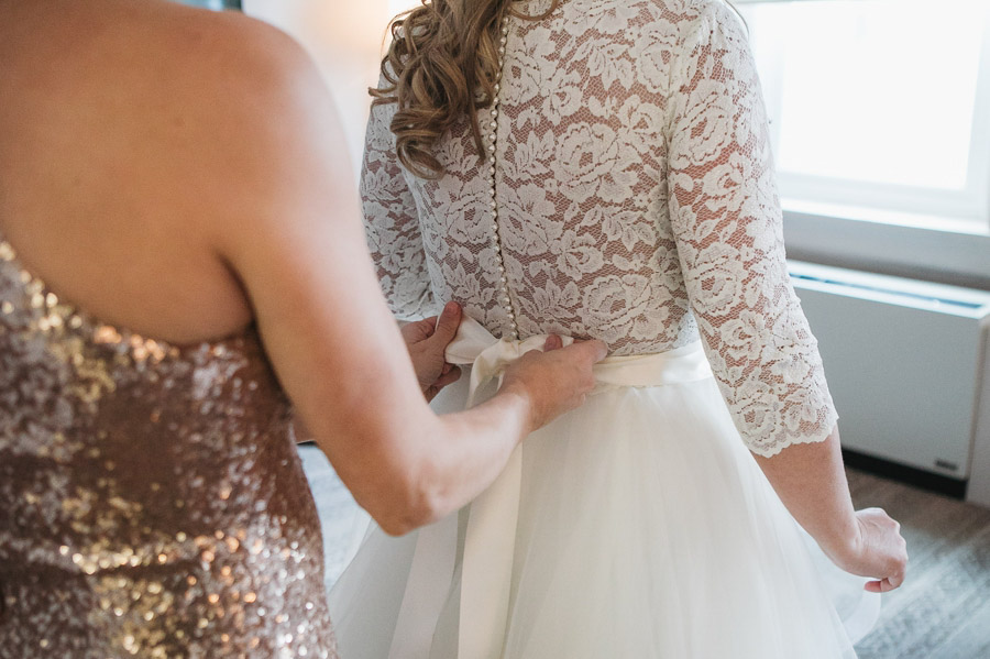 close up of brides dress being tied