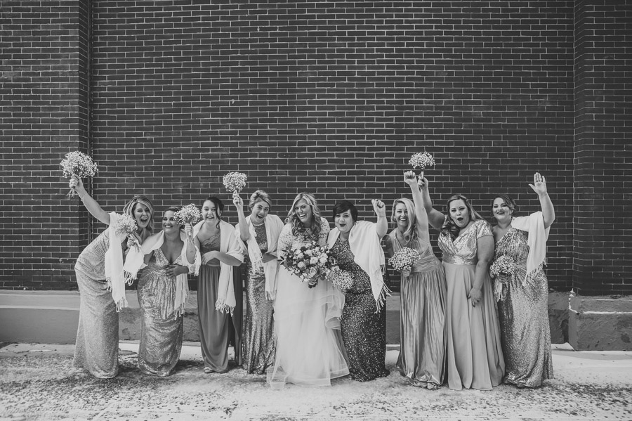 black and white photo of bride and bridesmaids cheering
