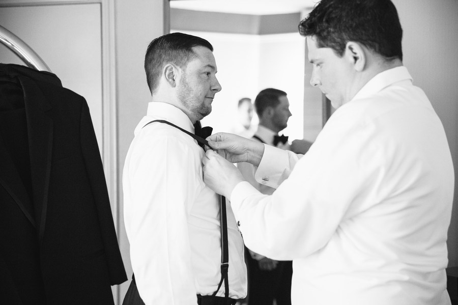 best man helping groom with suspenders