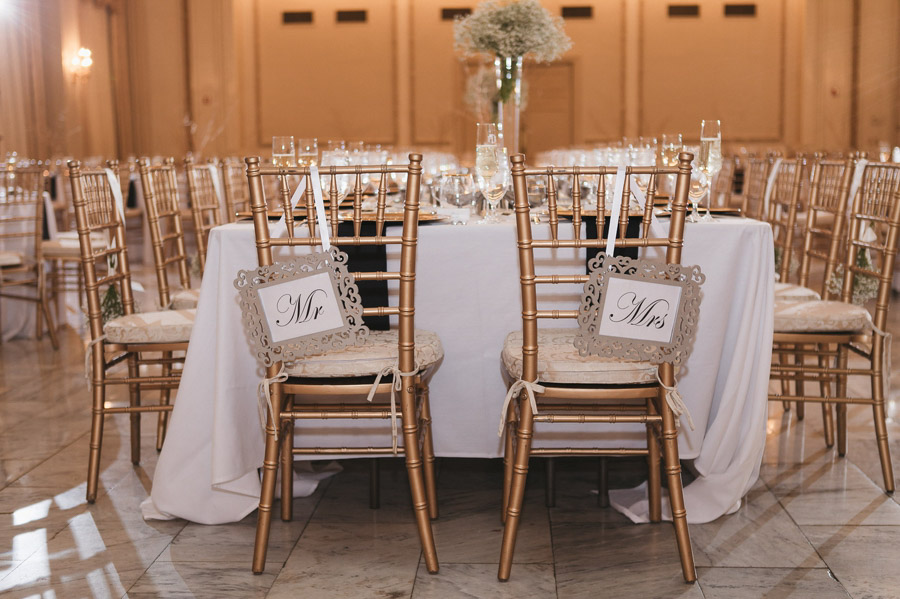 mr and mrs signs on gold chairs