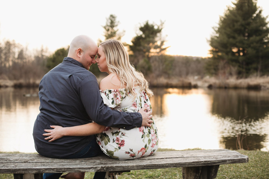 engaged couple sitting on bench at sunset in Mansfield Ohio