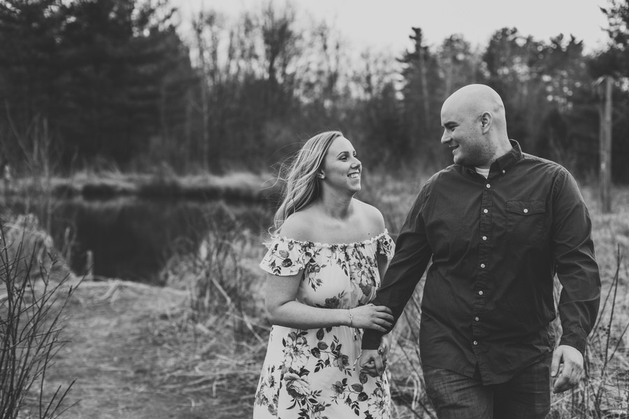 black and white photo of engaged couple skipping