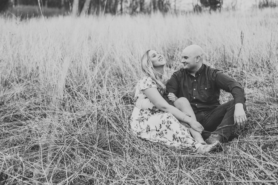 engaged couple laughing in grassy field