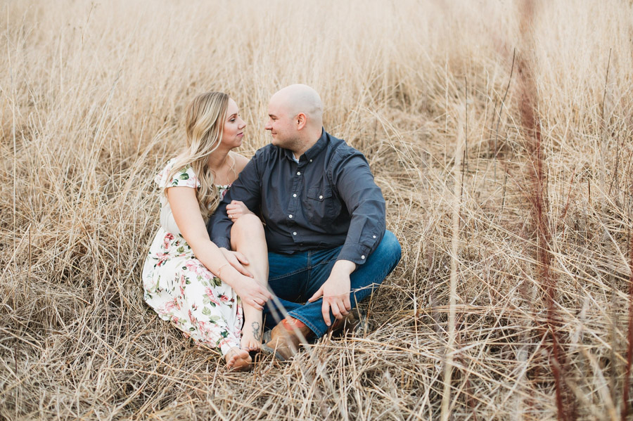 engaged couple looking at each other in grassy field