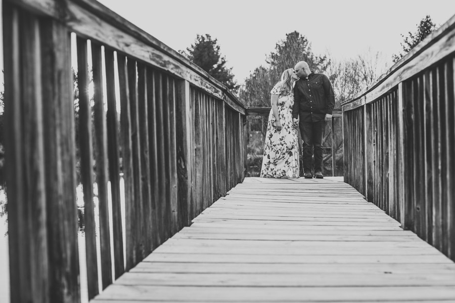 black and white photo of engaged couple kissing on dock