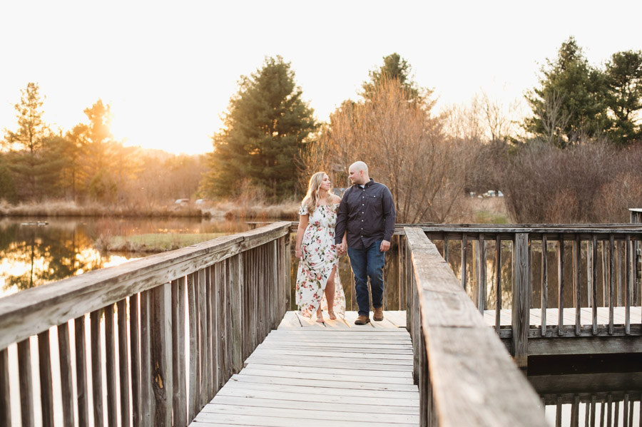 engaged couple walking together on dock