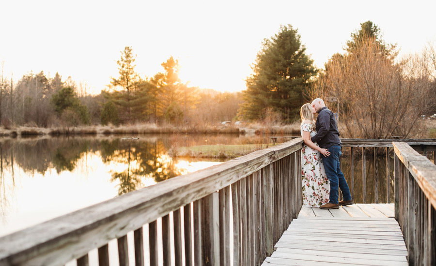 engaged couple kissing at sunset with pond in newark ohio
