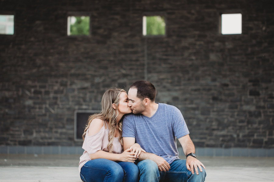 engaged couple kissing at scioto mile bicentennial park