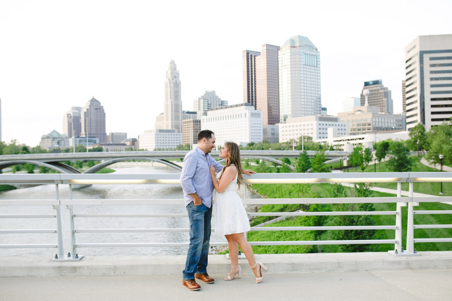 engaged couple looking at each other with columbus skyline