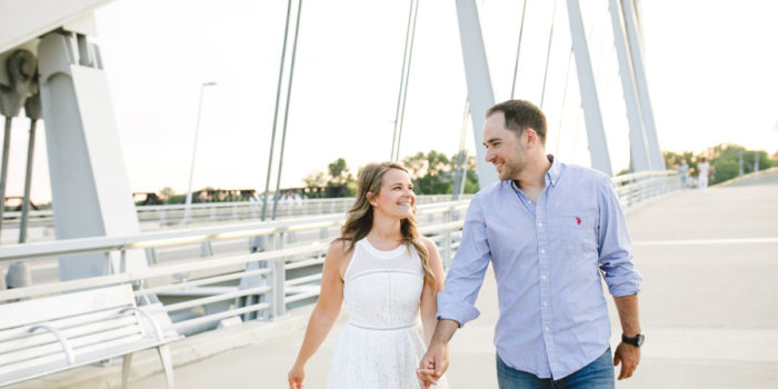 engaged couple walking together at scioto mile bridge