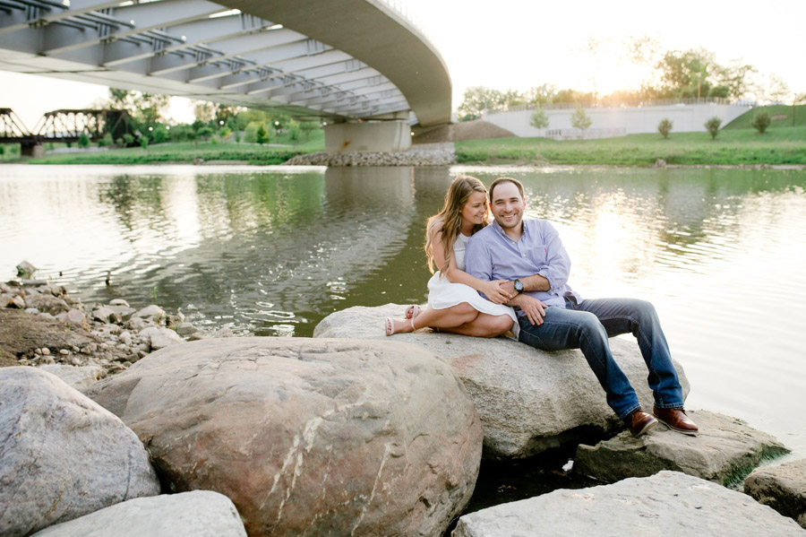 engaged couple sitting on rocks at scioto mile waterfront