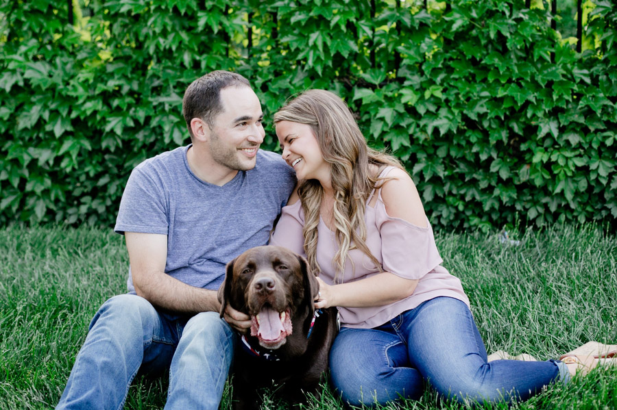 engaged couple laughing with dog at scioto mile bicentennial park