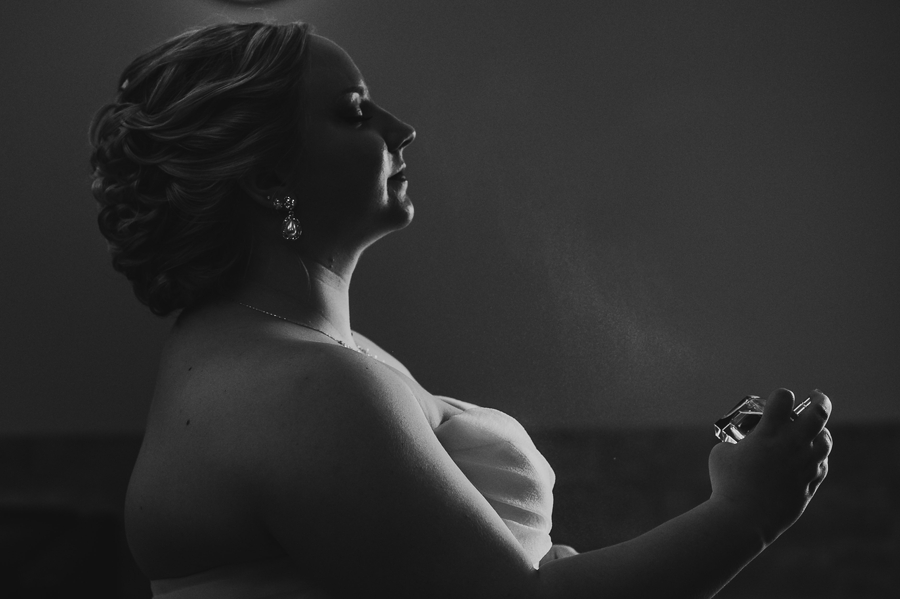 black and white photo of bride spraying perfume at Club at Corazon