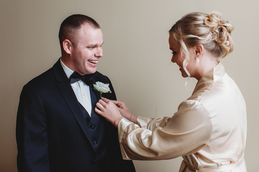 bridesmaid putting on grooms boutonniere